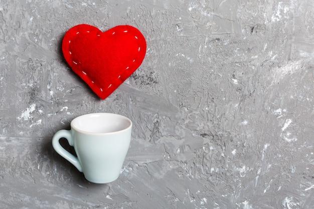 セメントの背景にカップからはねかける心の平面図構成。愛とロマンスのコンセプト。バレンタイン・デー