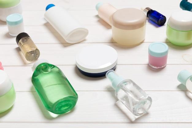 Косметические бутылки, банки, контейнеры и спреи на белом деревянном столе