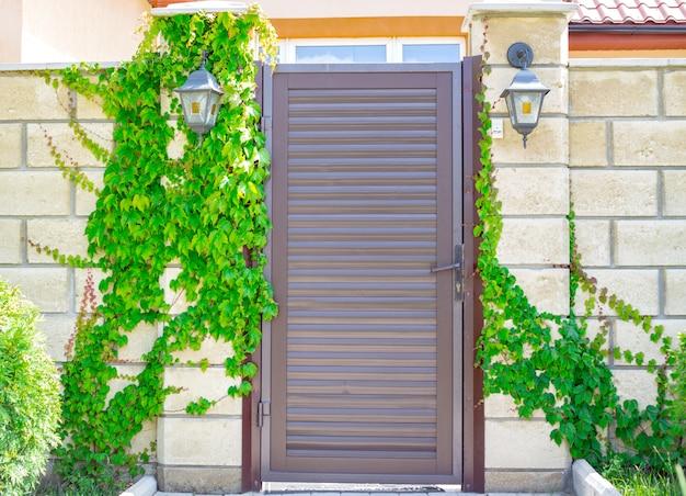村の開いた空の下でモダンな納屋の白いレンガ。アイロンボルトとロック付きの木製のドアは、登山植物で生い茂っています。晴れた日の夏の田園風景