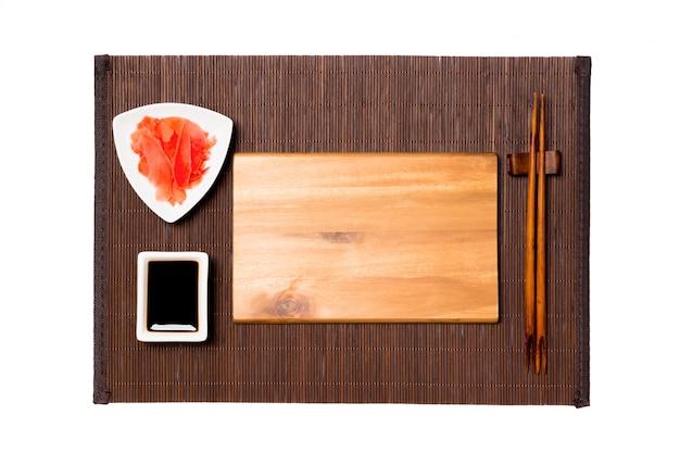 Пустая круглая черная тарелка с палочками для еды и соевым соусом, имбирь на циновке из темного бамбука
