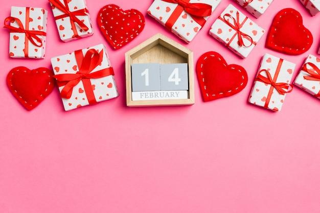Деревянный календарь в окружении подарочных коробок с бумажными сердечками и текстильными сердечками