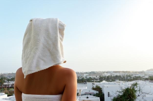 山を見下ろすテラスでシャワーを浴びた後、女性が彼女の頭の上にタオルで夕日を見る