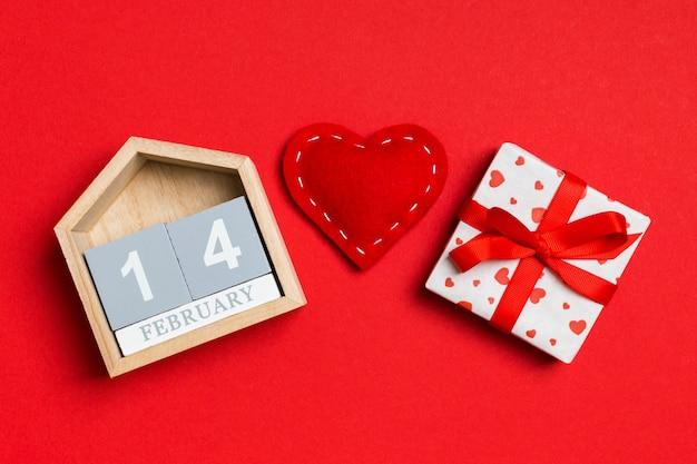 木製カレンダー、休日の白いギフトボックス、赤い繊維の心