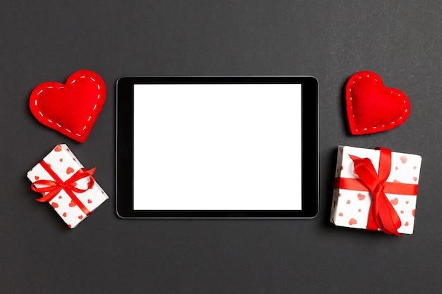 ギフトボックスと心に囲まれたデジタルタブレットのトップビュー