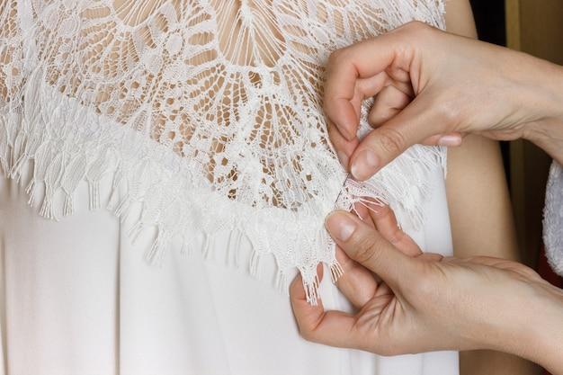 花嫁衣装のフィッティング。仕立て屋はフィッティングにドレスを準備します