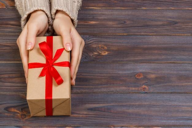 Женские руки дарят завернутый подарок на праздник ручной работы в крафт-бумагу с красной лентой.