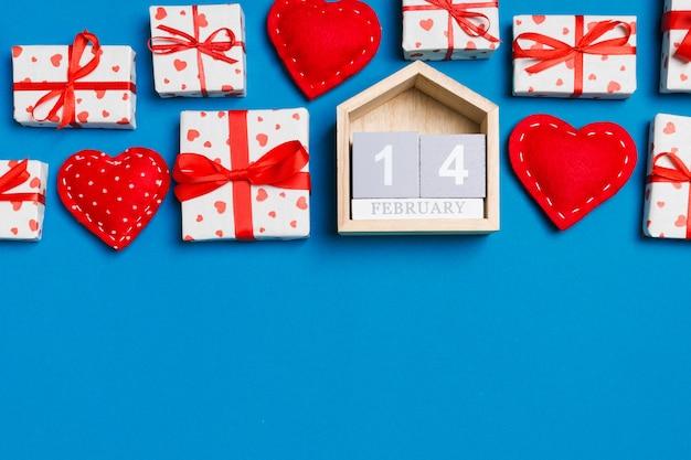 バレンタインのギフトボックス、木製のカレンダー、赤い織物の心の組成