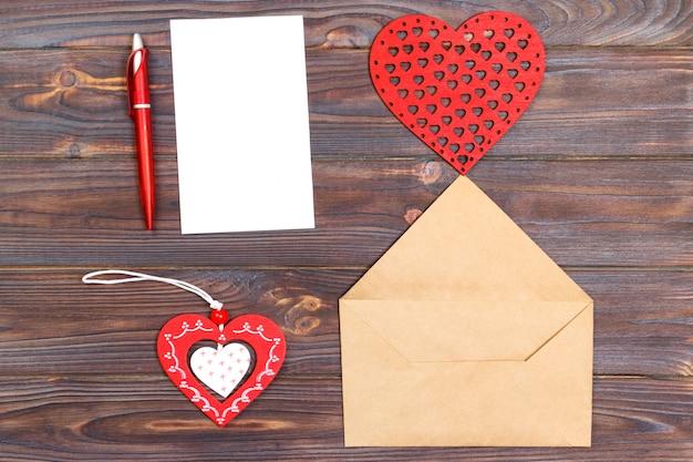 クラフト封筒、ペン、グリーティングカード、木のおもちゃの心、プラスチックの心とバレンタインの組成