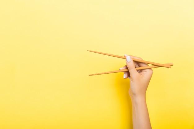 黄色の女性の手で保持されている木製の箸。空のスペースで概念を食べる準備ができて