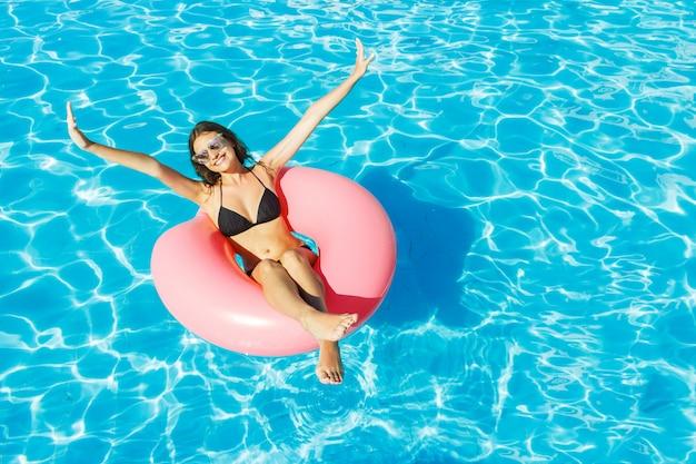 ビキニの若い幸せな女の子は、ピンクの円でプールで泳いでいます。