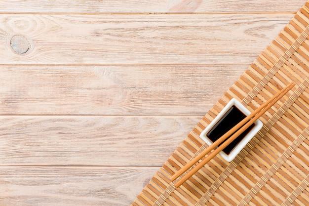 Бамбуковая циновка и соевый соус с суши палочками на деревянный стол. вид сверху с копией пространства фон для суши. плоская планировка
