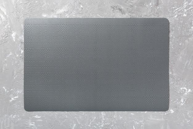 皿の黒いランチョンマットの平面図。セメントの背景
