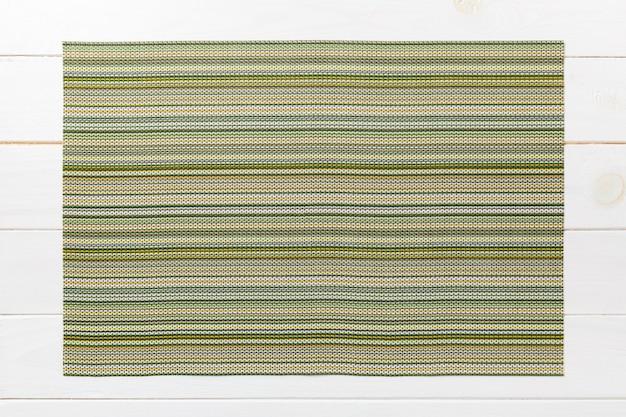木製のテーブルに緑のテーブルナプキンの平面図です。ランチョンマット