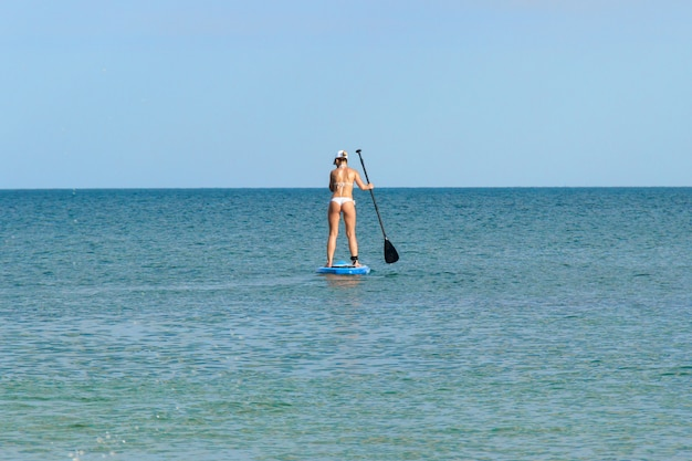 若い女性は青い水の中をパドルボーディングします。自由な時間を積極的に過ごす。海辺で素晴らしい夏休みを過ごす