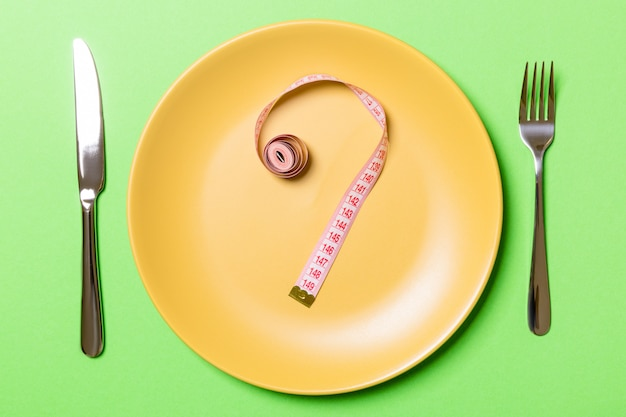 緑の背景の丸皿に巻尺で作られた疑問符。ためらいとダイエットの概念のトップビュー