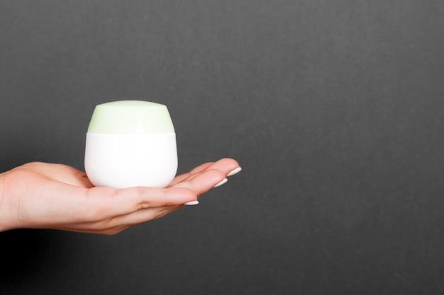 Крупным планом женская рука держит банку косметического продукта на черном фоне с копией пространства