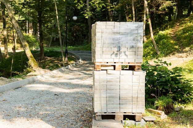 Куча бетонной тротуарной плитки на деревянный поддон. блоки для мощения тротуара в парке