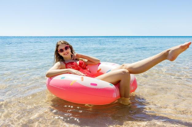 夏の晴れた日にビーチで膨脹可能なドーナツと泳いでいる女性