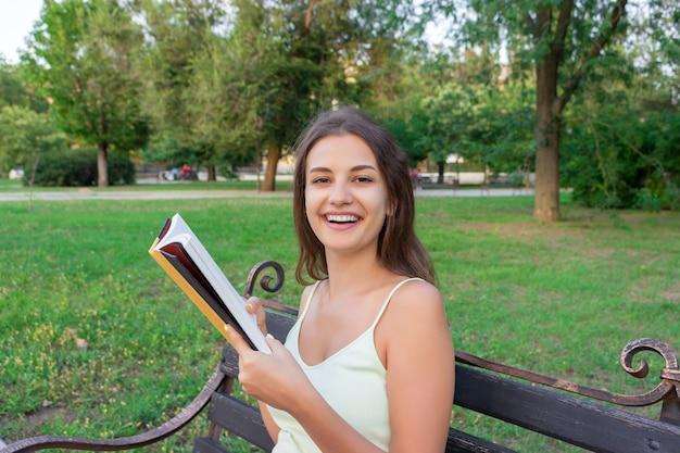 美しい若い茶色の髪の少女は本を読んでいて、新鮮な印刷本の香りを楽しんでいます