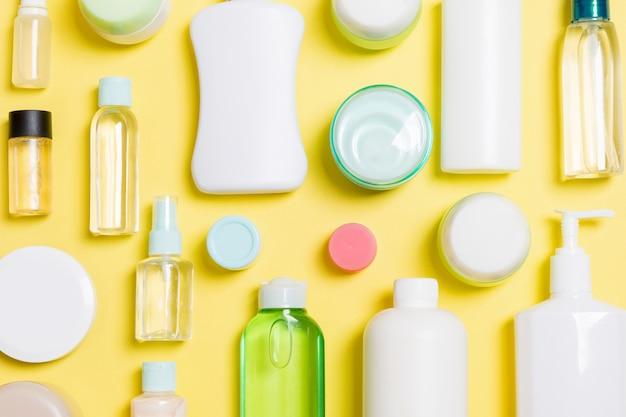 プラスチック製のボディケアボトルのグループは、設計のための黄色の背景の空スペースに化粧品と組成物を置きます。白い化粧品容器のセット