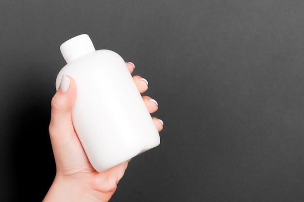 Крупным планом женская рука держит бутылку косметического продукта на черном фоне