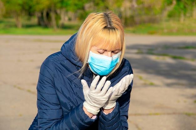 コロナウイルスとインフルエンザの発生中にフェイスマスクを着ている女性。患者の咳