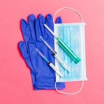 ピンクの背景に使い捨てサージカルマスク、ラテックス医療用手袋と注射器のペアの平面図です。コピースペースであなたの健康概念を保護してください