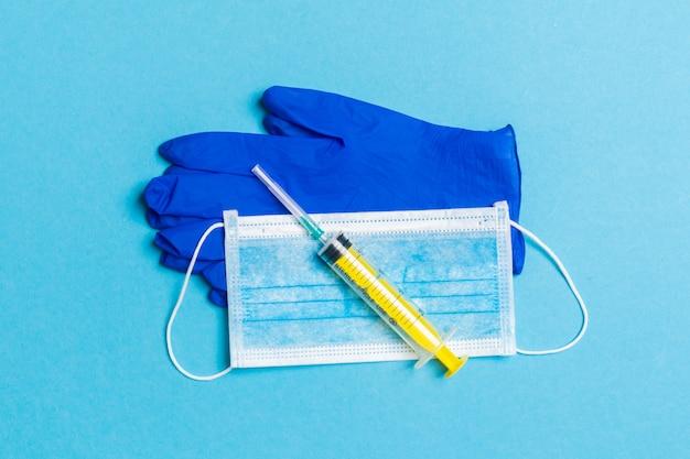 青の背景に使い捨てサージカルマスク、ラテックス医療用手袋と注射器のペアの平面図です。コピースペースを持つウイルス保護の概念
