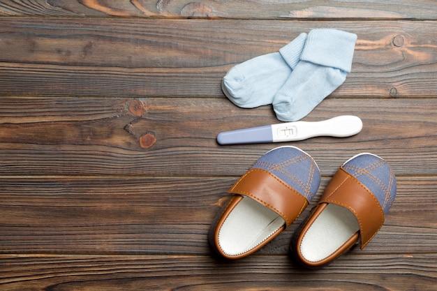 妊娠検査で肯定的な結果が得られ、新生児用の衣服、テキスト用のコピースペース。木製のテーブルに家族の概念のトップビューを拡張します。