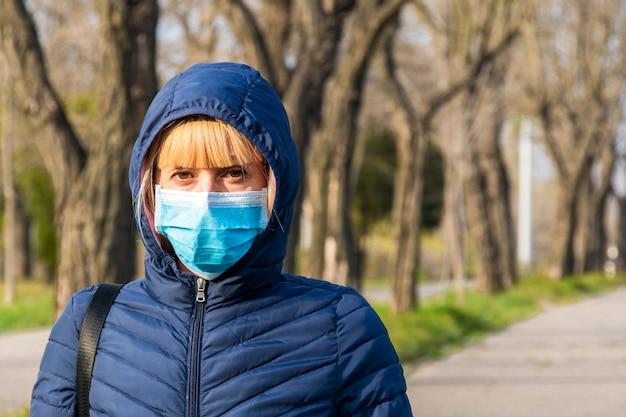 大気汚染が付いている都市の公園で防護マスクの若い女性