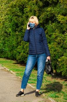 公園、コロナウイルスの概念でスマートフォンを使用して防護マスクを持つ女性