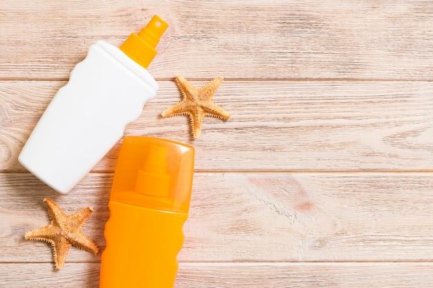 Взгляд сверху бутылки солнцезащитного крема с морскими звёздами на предпосылке деревянной доски с космосом экземпляра. плоская планировка летних путешествий