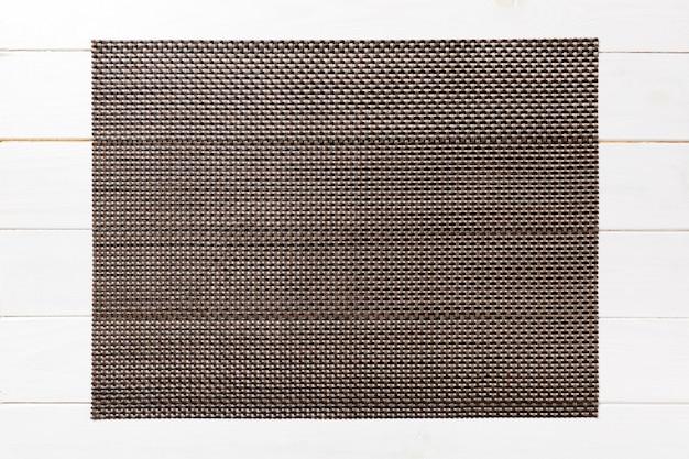 Взгляд сверху коричневой салфетки таблицы на деревянной стене. поместите коврик с пустым пространством для вашего дизайна