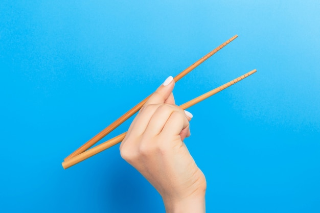 水色の壁に箸を持つ女性の手。あなたのデザインのための空のスペースを持つ伝統的なアジア料理