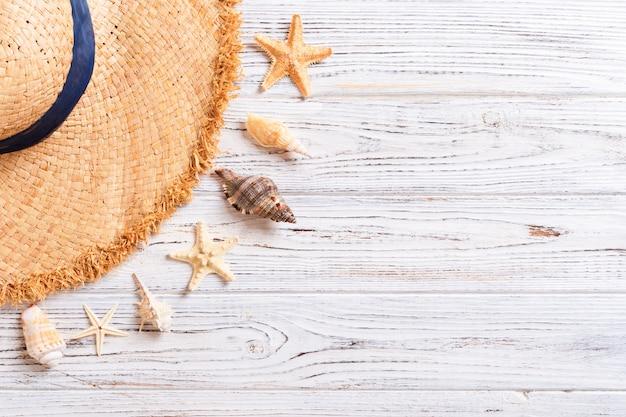 Пляжная шляпа с ракушками на коричневый деревянный стол. летняя стена концепция с копией пространства вид сверху