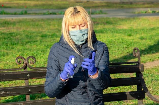 ウェットワイプの消毒で携帯電話の画面をクリーニングする公園の女性