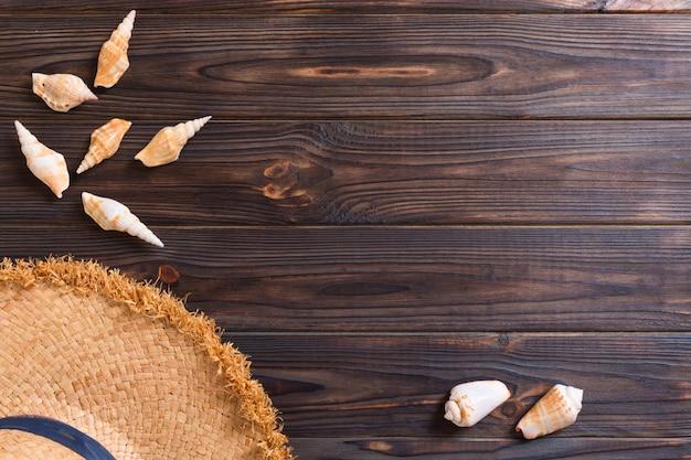 Летний праздник фон с соломенной шляпе и ракушками на деревянном