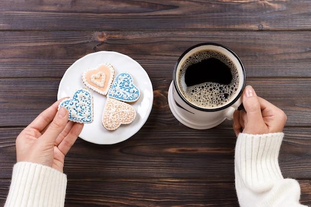 木製のテーブルにコーヒーとハート型のクッキーと女性の手