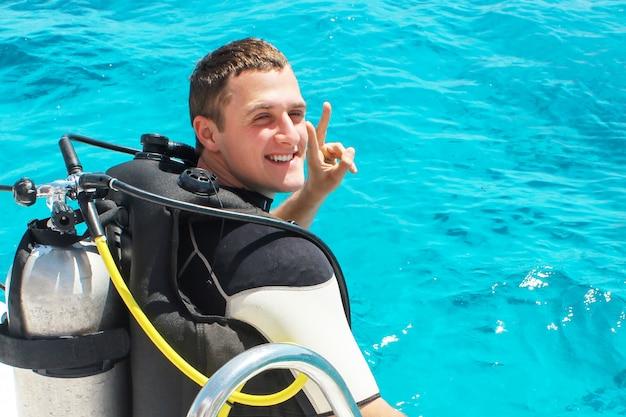 Аквалангист готовится к погружению в голубую воду с лодки