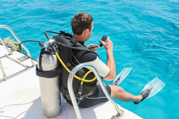 彼の水中カメラでヨットから海に飛び込む準備をしているダイバー