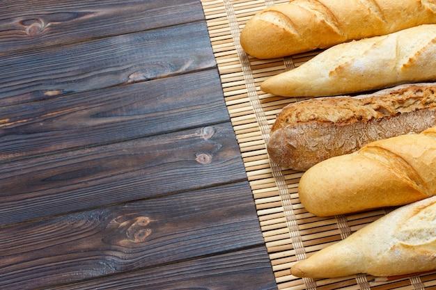 Свежеиспеченные французские багеты на белом деревянном столе. вид сверху