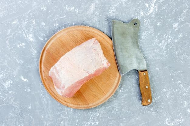 ナイフまたは台所斧でボード上の豚肩肉の生カット。