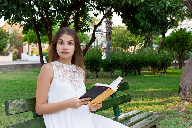Портрет крупного плана красивой удивленной девушки с широко раскрытыми глазами пока читающ книгу