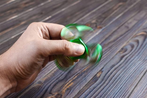 Руки держат игрушку популярного непоседа. волнующийся прядильщик