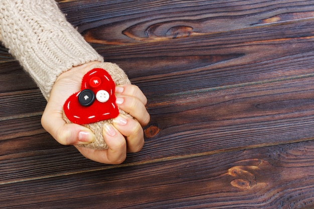 木製の背景に両手で心臓発作