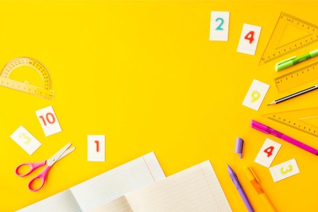 Тетради, ручки, карандаши, цифры и линейки на желтом фоне