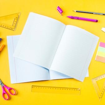 Тетради, ручки, карандаши и линейки на желтом фоне