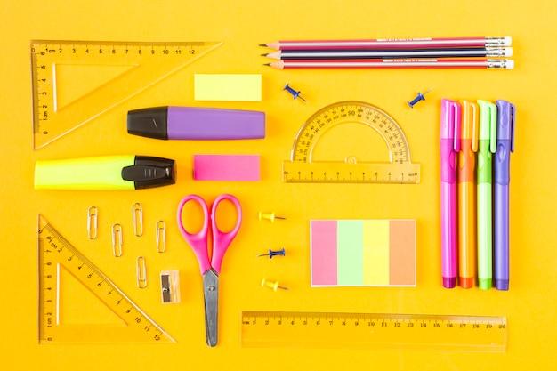 ペン、鉛筆マーカー、ボタン、ペーパークリップ、黄色の背景に定規