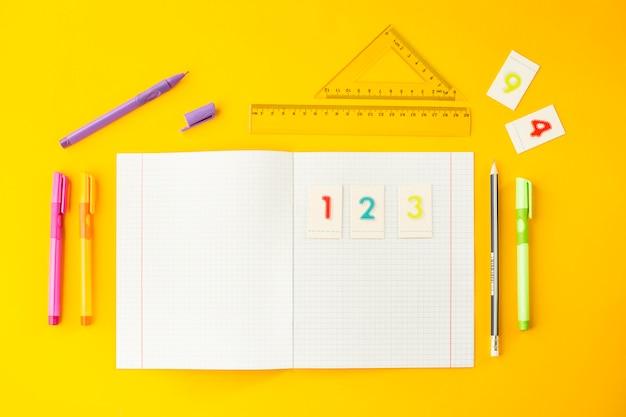Тетрадь в клетке среди ручек, карандашей, цифр и линейок на желтом фоне