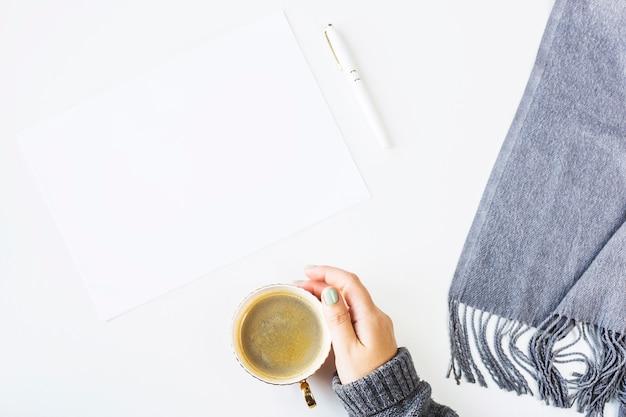 秋はスカーフと一杯のコーヒーの横にある白いテーブルにモックアップ